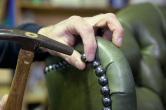Close up of upholsterer applying studding to traditional furniture