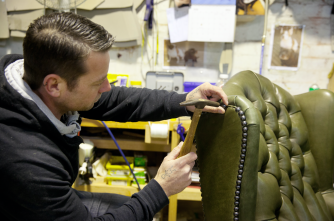 Upholsterer applying studding to traditional furniture